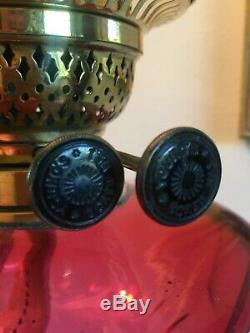 Late 19th century oil lamp with Cranberry Reservoir on a Corinthian brass column